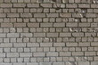 Old shabby, wrecked brick wall with grey cement mortar as background
