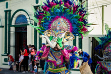 Native Man Puts On Heavy Colorful Elephant Mask On City Street At Dominican Carnival