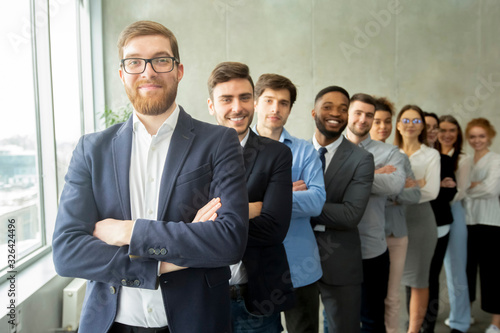 Happy business team headed with boss standing in row