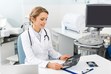 professional smiling doctor looking at ultrasound scan in clinic