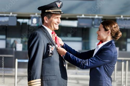 Young attractive flight attendant adjusting pilot neck tie in airport Wallpaper Mural