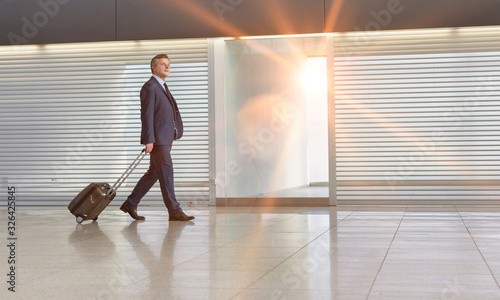 Mature businessman walking with his suitcase in the airport Wallpaper Mural