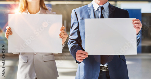 Photo Business people standing while holding blank white placard in arrival area at ai