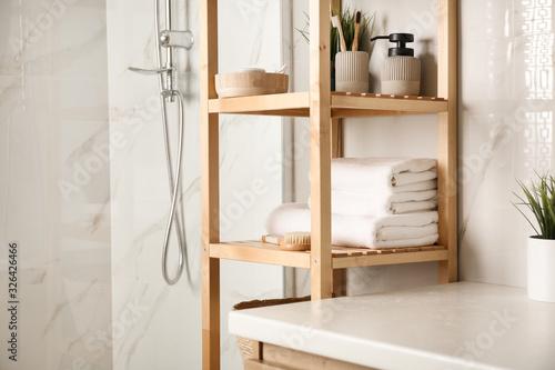 Fototapeta Shelving unit with clean towels in bathroom interior obraz