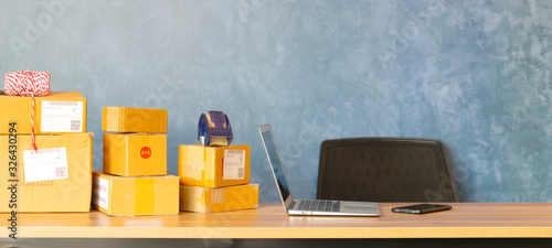 Obraz Laptop computer at workplace of start up, small business owner. cardboard parcel box of product for deliver to customer. Online selling, e-commerce, packing concept, Morning ligh. - fototapety do salonu