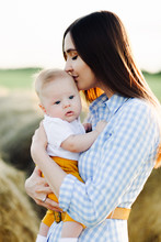A Young Happy Mother With A Small Child In Her Arms, Gently Kissing His Head, Stands In The Middle Of A Field Near A Collected Haystack In The Rays Of The Setting Sun