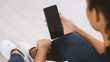 Leinwanddruck Bild - Young sporty woman holding mobile phone with blank screen indoors, closeup view. Mockup for design
