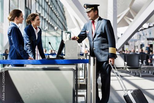 Fényképezés Portrait of mature pilot talking with the airport staffs in boarding gate