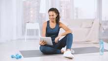 Beautiful Hispanic Woman With Tablet Computer Watching Workout Video On Yoga Mat At Home