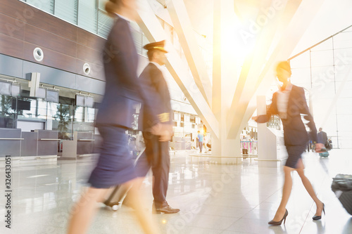 Mature pilot with young beautiful flight attendants walking in airport Wallpaper Mural