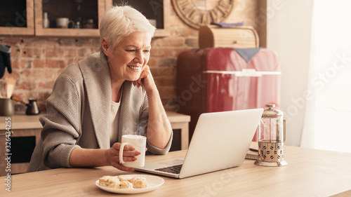 Fényképezés Happy Aged Lady Relaxing In Kitchen With Laptop And Coffee