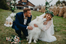 Newlyweds Play With Dog On Background Of Lawn And House.