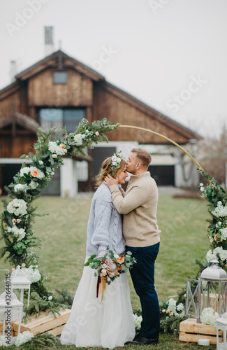 Newlyweds stand near wedding arch at lawn. Wallpaper Mural
