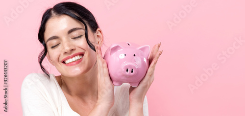 Cuadros en Lienzo Young woman with a piggy bank on a pink background