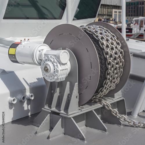 Foto powerful anchor winch with a new iron chain on the deck of a large boat