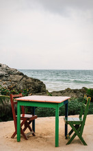 Green Painted Table And Chairs Set Up On Beach