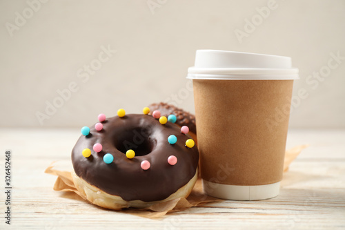 Fototapeta Delicious glazed donuts and coffee on white wooden table obraz