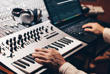 Music Producer Hands Composing A Song On Synthesizer Keyboard And Laptop Computer In Recording Studio