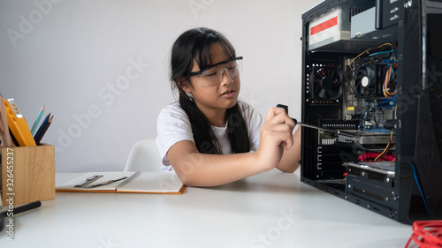 Valokuva Photo of young adorable girl fixing/installing a computer hardware at the modern white working desk