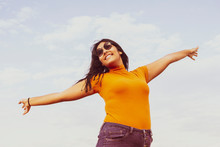 Young Curvy Woman In A Casual Outfit With Blue Sky Background