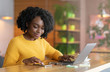 Positive afro businesswoman working online and using mobile phone