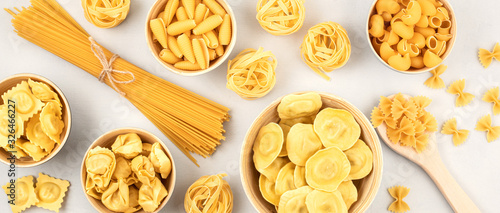 Fototapeta Flat lay with different types of traditional italian pasta. Penne, tagliatelle, fusilli, farfalle, spaghetti and others. Traditional italian cusine concept. Top view obraz
