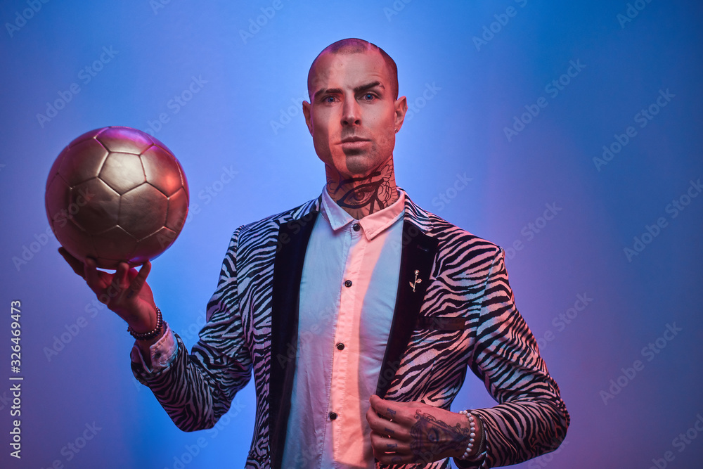 Fashionable, handsome, tattooed, bald male model posing in a studio for the photoshoot wearing fashionable custom made zebra striped style tuxedo and rose patterned shirt, holding a golden soccer ball
