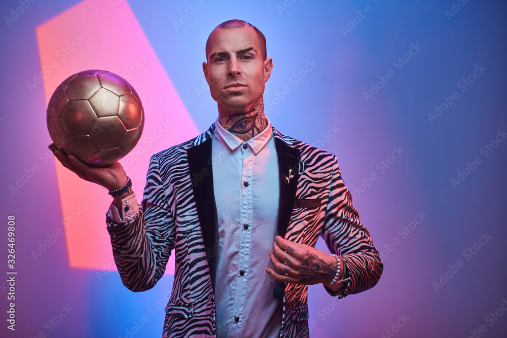 Fit, handsome, tattooed, bald male model posing in a studio for the photoshoot wearing fashionable custom made zebra striped style tuxedo and rose patterned shirt, looking on a camera, holding a
