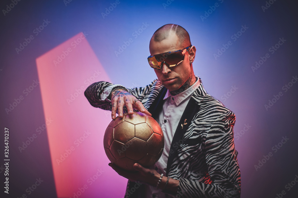 Fashionable, handsome, tattooed, bald male model posing in a studio for the photoshoot wearing fashionable custom made zebra striped style tuxedo, glasses and rose patterned shirt, looking on a golden <span>plik: #326470237 | autor: Fxquadro</span>
