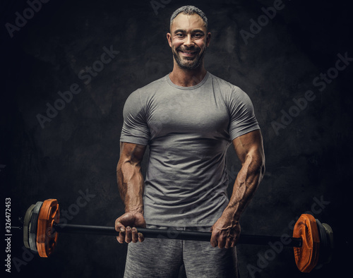 Strong, adult, fit muscular caucasian man coach posing for a photoshoot in a dar Canvas Print