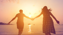 Happy Couple Holding Each Other Hands Walking To The Sea At Sunset.