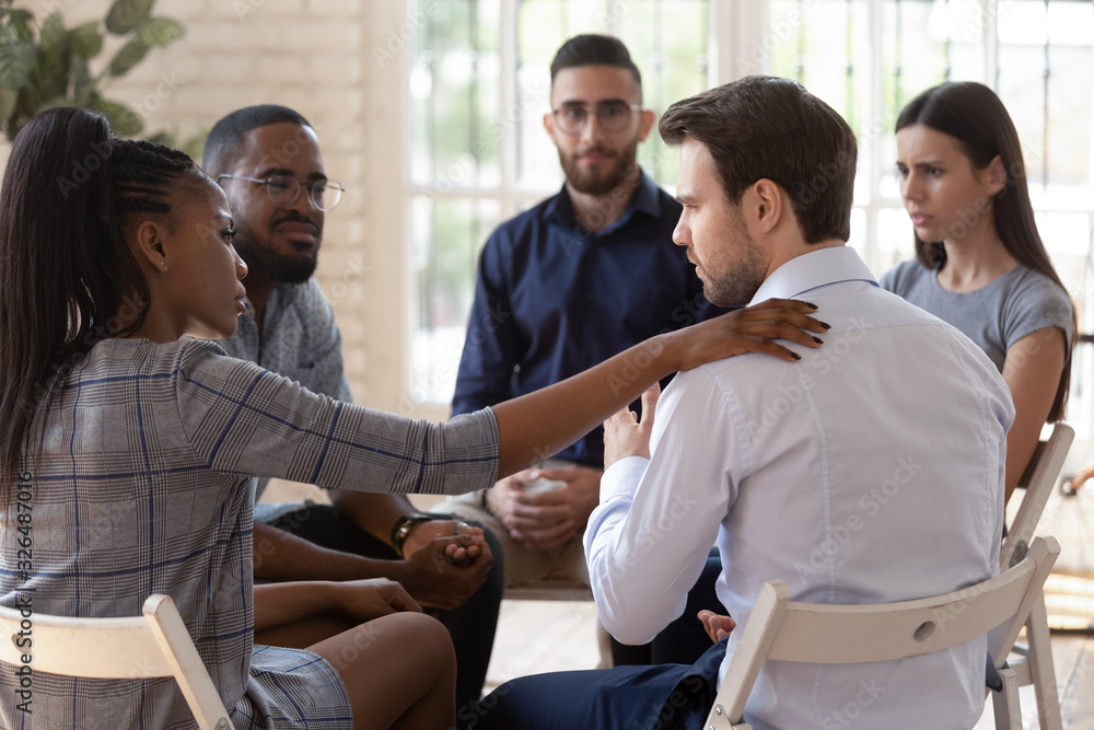 Fototapeta African psychologist supporting caucasian male rehab session participant