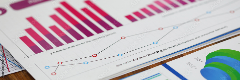 Fototapeta Close-up of biz documents with statistics data in charts, graphs and diagrams. Financial forecast of growth income. Stock Exchange, Securities Market concept. Blurred background