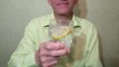 Man holds a drink in a glass with ice and lemon
