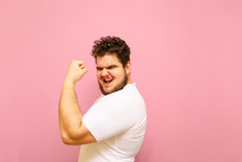Joyful Fat Man Showing Biceps And Looking Into Camera With Smile On Face Isolated On Pink Background. Portrait Of A Big Boy Overweight, Happy To Win With His Arm Raised And Posing For The Camera.