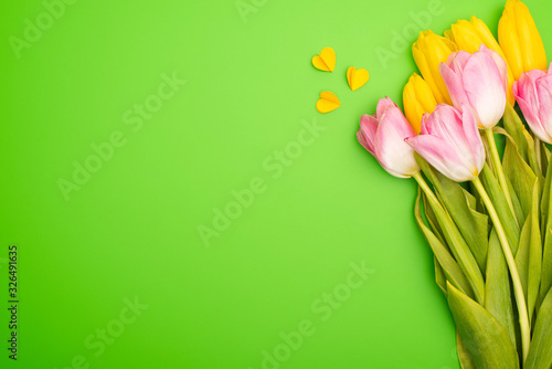 Top view of bouquet and colorful decorative hearts on green, spring concept - 326491635