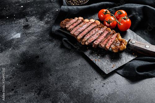 Fototapeta Grilled sliced strip loin steak on a meat cleaver. Black background. Top view. Copy space obraz