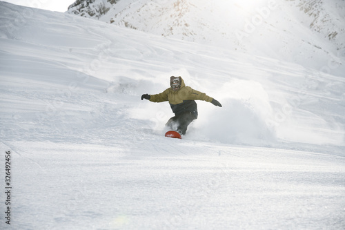 Photo Snowboarder in anorak rides on a snowboard in mountains