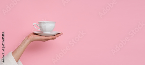 Obraz Coffe please. Female hand holding a cup of coffee isolated on pink background. Time to charge battery. - fototapety do salonu
