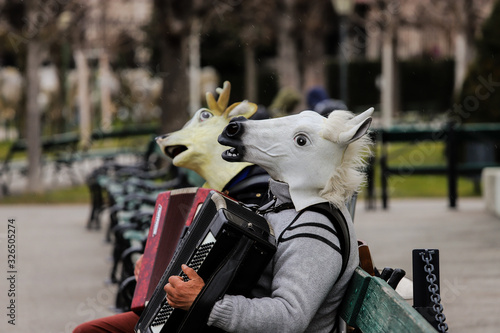 People on a bench in Vienna playing the accordion with a horse and deer mask Canvas Print