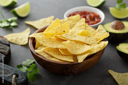 Fotomural Tortilla chips in a bowl with salsa, limes and avocados