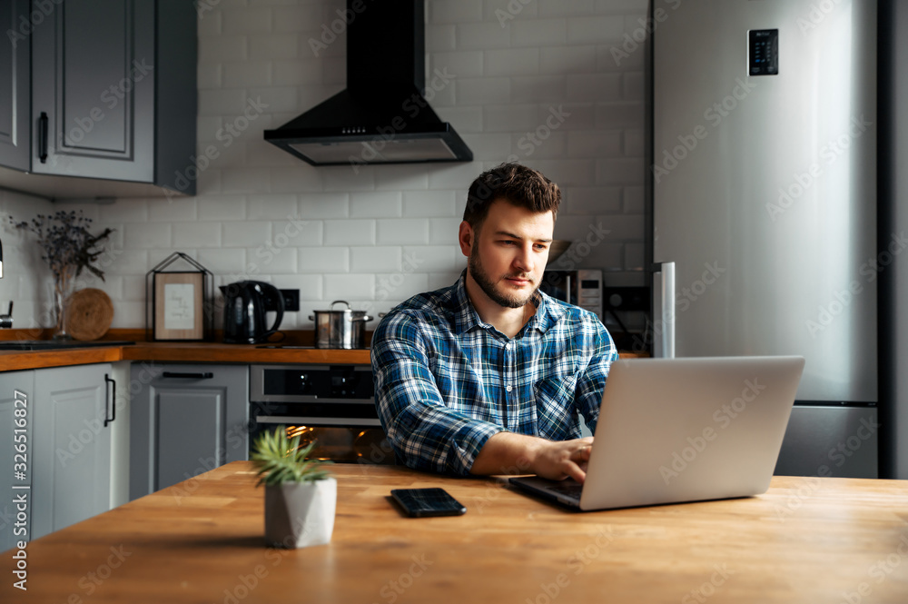 Fototapeta Young male freelancer works from home