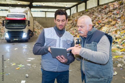 Slika na platnu two male workers looking at tablet pc in refuse center