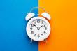 White vintage alarm clock on blue-orange background. Top view, copy space. Daylight saving concept.