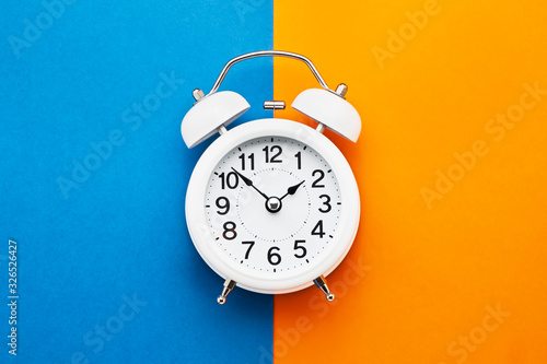White vintage alarm clock on blue-orange background. Top view, copy space. Daylight saving concept. - 326526427