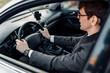 Attractive elegant young businessman driving a car