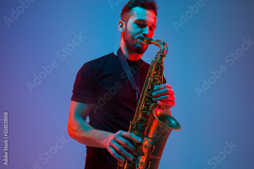 Young caucasian jazz musician playing the saxophone on gradient blue-purple studio background in neon light Wallpaper Mural