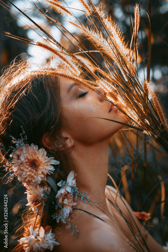 close up portrait of young and tender woman on a feild at sunset Wall mural