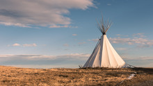 Traditional Native American Nomadic Teepee In The Grassy Plains At Sunset And Beautiful Landscape Background
