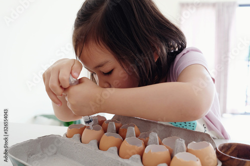 Fotografia, Obraz Mixed Asian girl planting seeds into eggshells, eco gardening,  homeschool monte